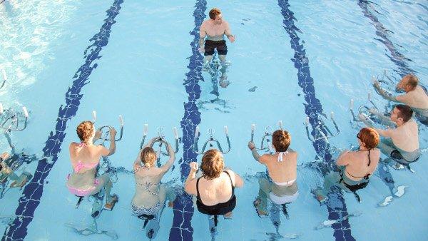 Plusieurs sportifs assistent à une séance d'aquabiking avec un coach